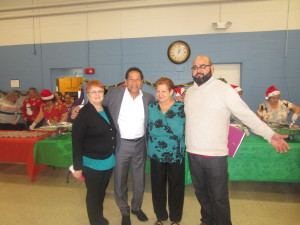 State Rep. Carlos Gonzalez and City Councilor Adam Gomez with friends at the Riverview Apartments.
