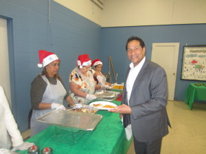 State Rep. Carlos Gonzalez, who co-hosts the event with the Riverview Tenants' Council, delivers lunch with a flourish to elderly residents.