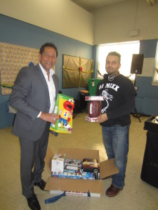 State Rep. Carlos Gonzalez and local DJ Carlos Gonzalez, no relation, hold up gifts for the young grandchildren of participating partygoers.