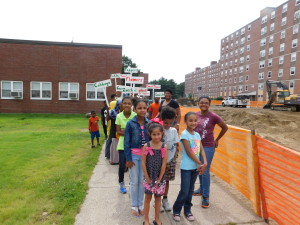 Children in the youth program at Riverview Apartments walk towards the community garden with the signs they made for elderly gardeners.