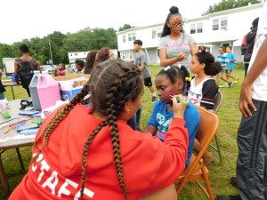 Teens at Robinson Gardens Apartments painted faces on the younger set.